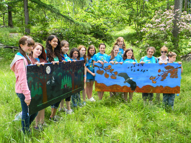 Members of GFMS Go Green Club show off two of the four murals they painted for the Mount Nimham fire tower's cabin